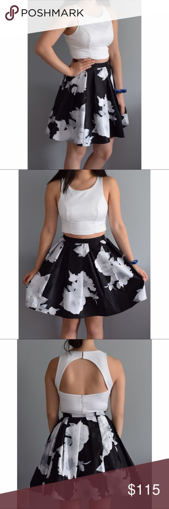 Black and white two piece dress Worn once. It is a size 1 and in good condition. The skirt is black with white flowers and the top is a white silky material with an open back. Price is negotiable. Dresses Prom