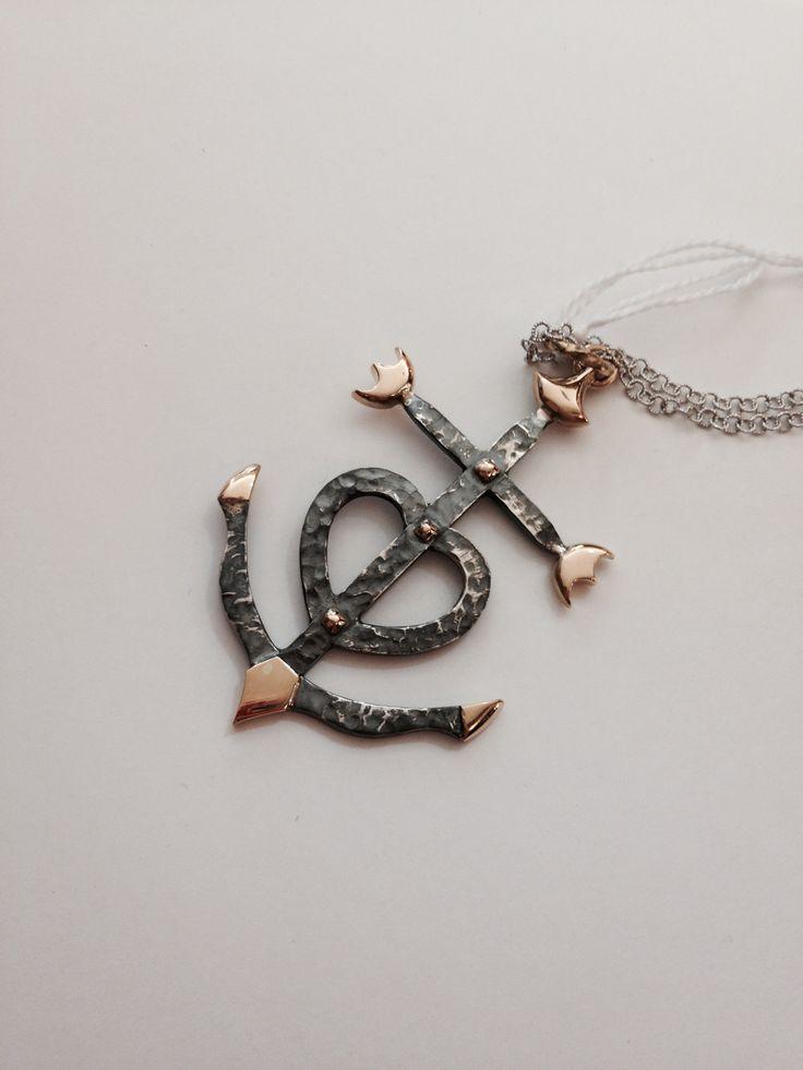Pendente in oro rosa e argento brunito e martellato che rappresenta la Croce della Camargue. Questo simbolo raffigura tre virtù: la Fede (la croce latina), la Speranza (l'àncora) e la Carità (il cuore)
