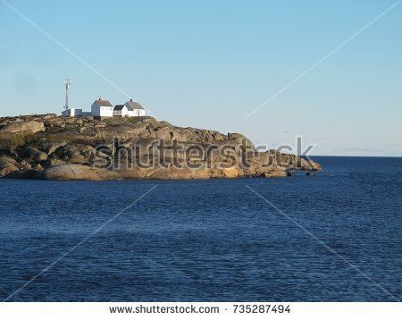 sea island with white buildings. Stavernsodden Lighthouse. Norway.