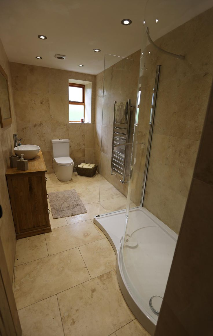 downstairs loo and shower room, oak vanity unit with free standing sink, travertine tiles, basket for toilet rolls
