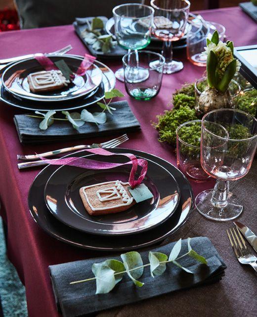 Tischgedeck, u. a. VARDAGEN Teller in Dunkelgrau, mit Pfefferkuchengebäck und einem Eukalyptuszweig