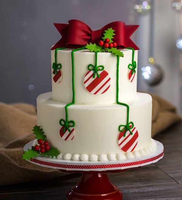 Christmas tree themed Christmas cake. The Christmas cake is designed to look like a Christmas tree complete with a mistletoe and Christmas balls hanging around the tree. On top the icing has been designed to look like a ribbon.