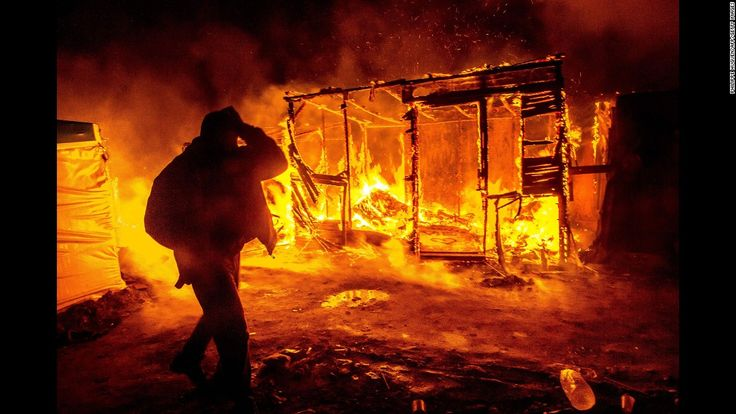 """A migrant walks past a burning shack in the southern part of the """"Jungle"""" migrant camp in Calais, France, on Tuesday, March 1. Part of the camp was being demolished -- and the inhabitants relocated -- in response to unsanitary conditions at the site."""