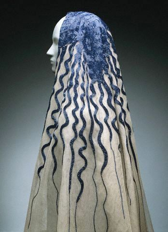 "This veil topped the wedding dress that closed Schiaparelli's 1938 Circus collection. Bugle beaded ""hair"" resembles Medusa's snakes and can be read as Schiaparelli's take on marriage."