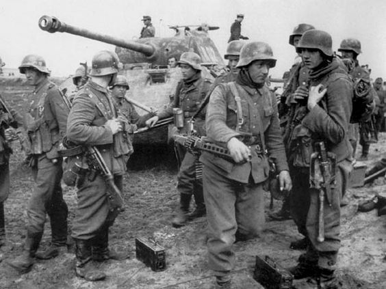 """Waffen SS Panzergrenadiers of the Viking Division prepare for battle near Kovel in the Ukraine, April 1944. Note the grenadier in the foreground carrying the MG-42 light machine gun and the soldier to the left armed with the StG-44 """"Stug"""" assault rifle."""