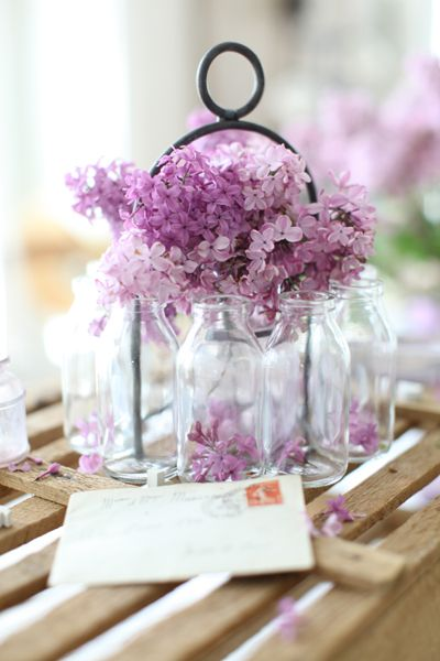 Milk bottle caddies with flowers can create a unique and elegant centerpiece. www.dreamywhitesonline.com