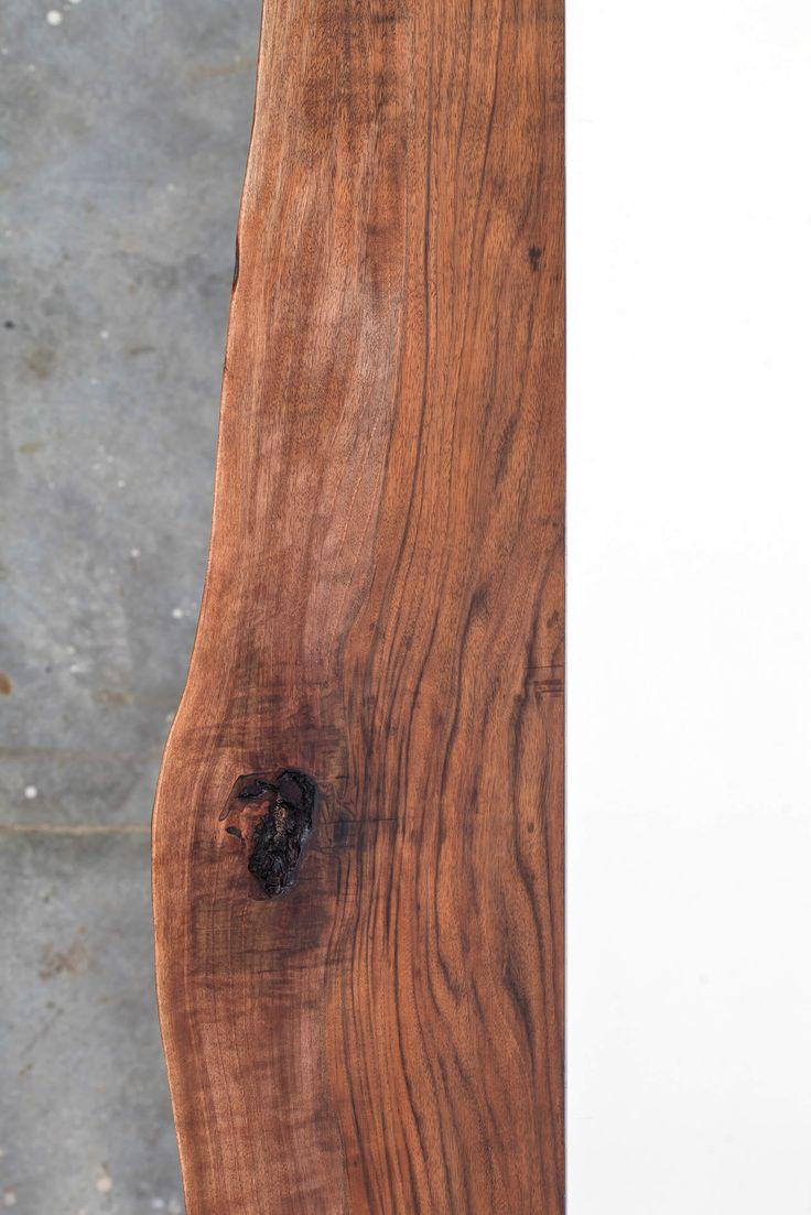 Tavolo realizzato da due sezioni di Noce nazionale unite da un inserto in acrilico bianco. Struttura in ferro colorato e gambe in acciaio lucido.