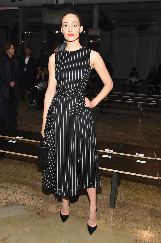 Carolina Herrera dressed Emmy Rossum in a Spring 17' black pinstripe tea length dress to the Fall Winter '17 show in New York on Monday, February 13th.