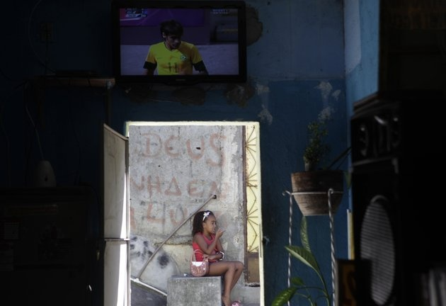 Mexico vs. Brazil soccer - Brazilian soccer player Neymar is seen on a TV screen at a bar in Turano slum as a girl sits outside during Brazil's game against Mexico at the London 2012 Olympic Games men's soccer final gold medal match in Rio de Janeiro August 11, 2012. REUTERS/Ricardo Moraes