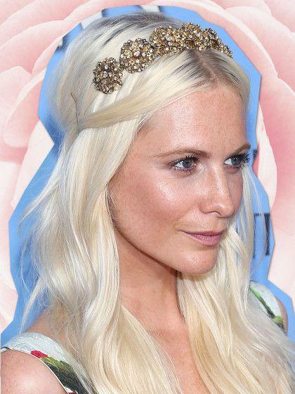 Aus der Romantik-Abteilung kommt diese Frisur von Poppy Delevingne: Leichte Wellen im Haar, Mittelscheitel, zwei Deckhaarsträhnen seitlich festgesteckt und eine Blumen-Tiara mit weißen Glitzersteinen.