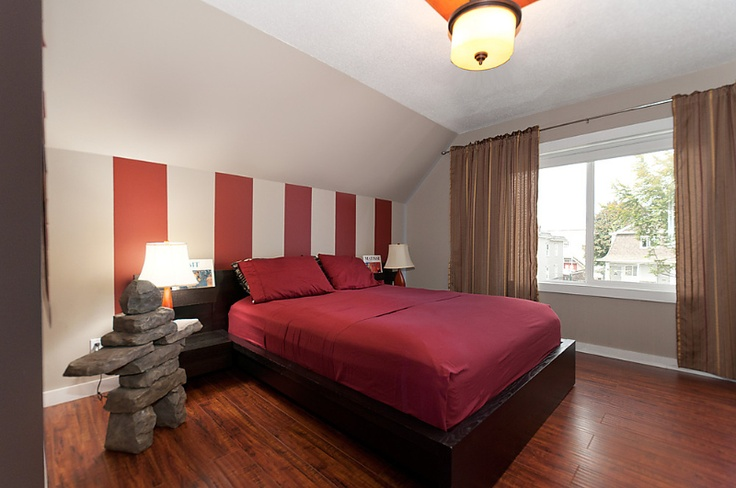 The generous-sized bedroom with its low-platform bed features vaulted ceiling and dynamic wall colors. As well as the Inukshuk that gives this apartment its name.  #Vancouver #Hotels #Rental #Accommodations