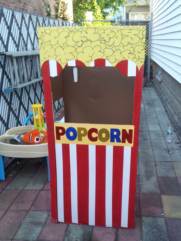 For my son's first birthday (circus theme) we decided to make a popcorn stand. We used a large cardboard box, red spray paint, white painters tape for the lines and yellow posterboard. It was easy to make and the kids loved taking pictures inside.