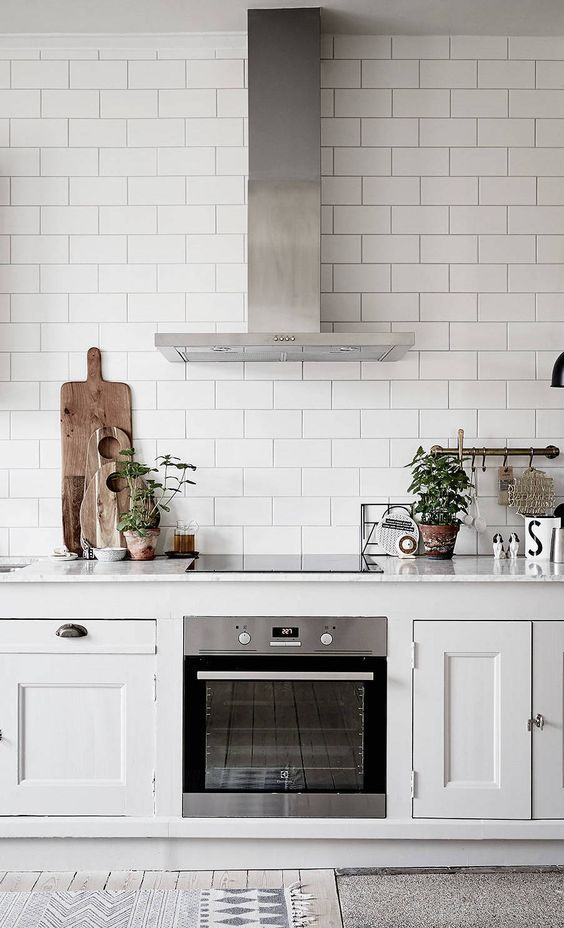 white subway tile all the way up, white units, stainless steel hood and oven, wooden chopping boards