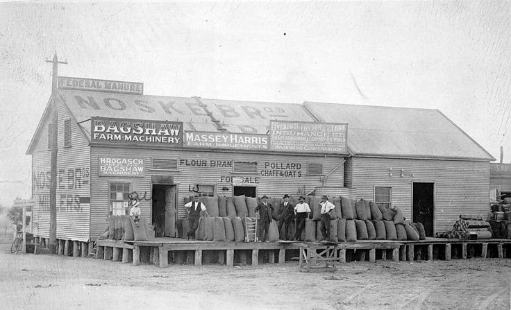 Noske Brothers Flour Mill at Rainbow in 1915. There are a number of men standing on a raised platform where there is a stack of grain sacks. Advertising signs on the building including: Federal manure, Bagshaw farm machinery and Massey Harris.