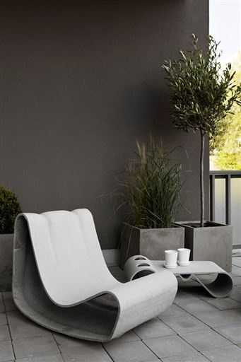 A cool grey space with grey planters. Lots of grasses, bay tree's, olive tree's, lemon & citrus plants.