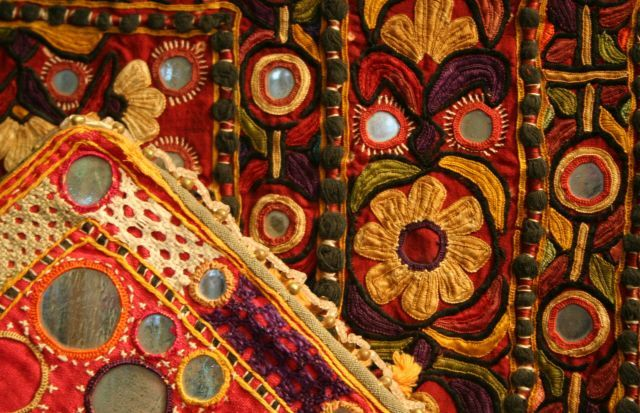 Detail of brightly cloured Indian objects embellished with embroidery, applique and mirrorwork. From the World of Textiles collection at Bankfield Museum © Calderdale MBC