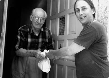 Meals on Wheels volunteer delivering meal to elderly man.