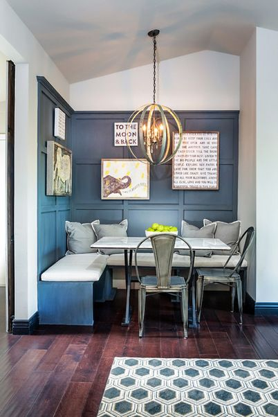 Traditional with an industrial twist breakfast nook with built-in banquette, navy walls, metal chairs, hardwood floors and pendant lighting | Dettaglio Interior Design