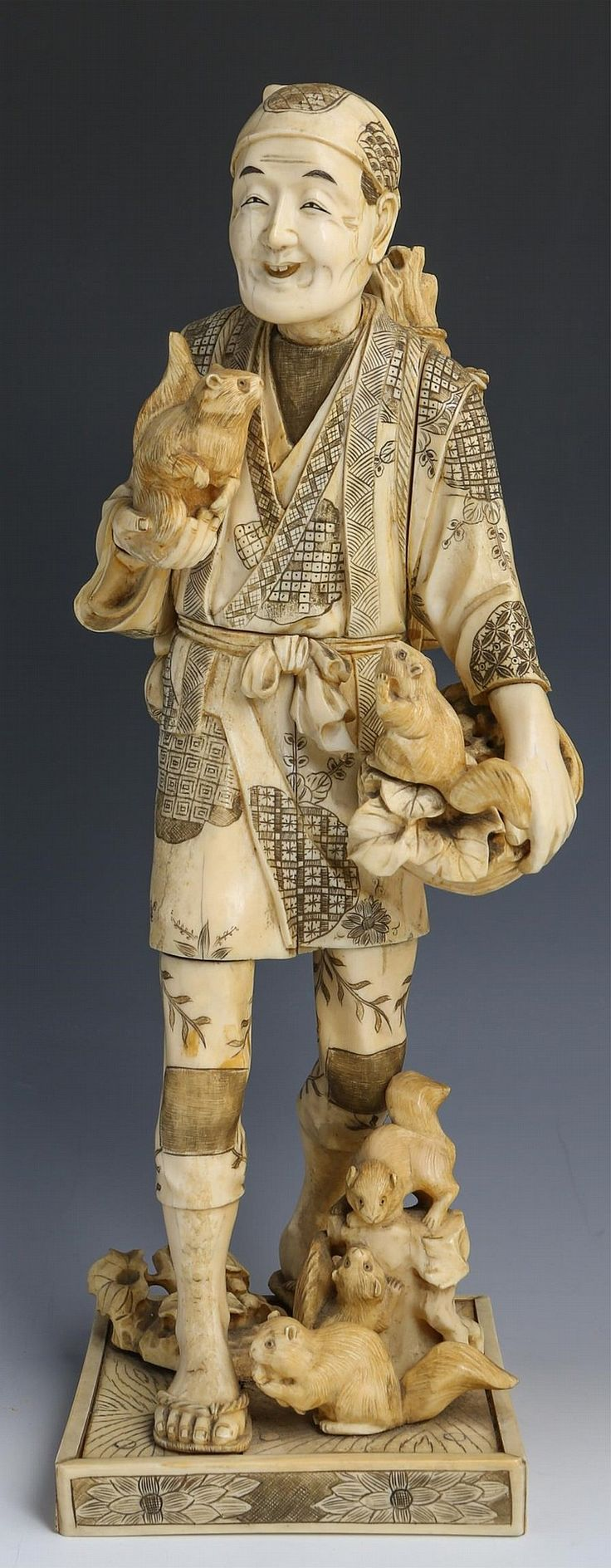 """JAPANESE CARVED IVORY OKIMONO MAN W SQUIRRELS Large Japanese carved ivory okimono, mid to late 19th C., depicting a walking man with a basket of fruiting branches and a dray of squirrels; a basket of branches at his back. Highly detailed with monochrome staining to enhance features. Red cartouche with signature on underside. Fitted to base with peg in foot. Provenance: Private Minnesota estate. Weight: 6.2lbs Size: 15.5 x 5"""""""