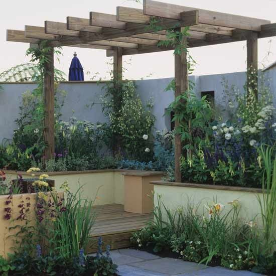 Small garden with wooden pergola    This pretty garden was designed for Tatton Park Flower Show. A shady corner is created by a large wooden pergola over raised decking. Rendered walls give the feel of an outdoor room, while plenty of climbers and plants create a cosy space. Planks of wood along the top of the wall provide a handy place to sit and enjoy the setting