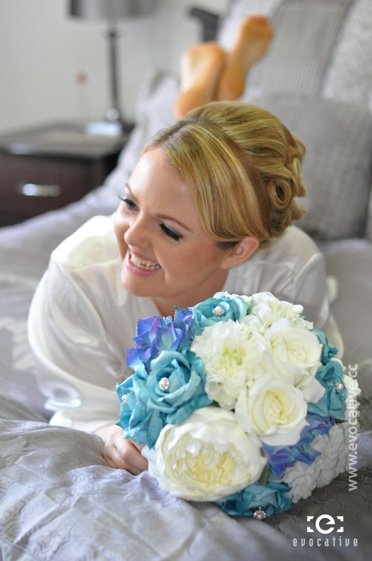 Alison the happy bride on the bed with her flower bouquet, beaming with excitement on her wedding day. #WeddingPhotography