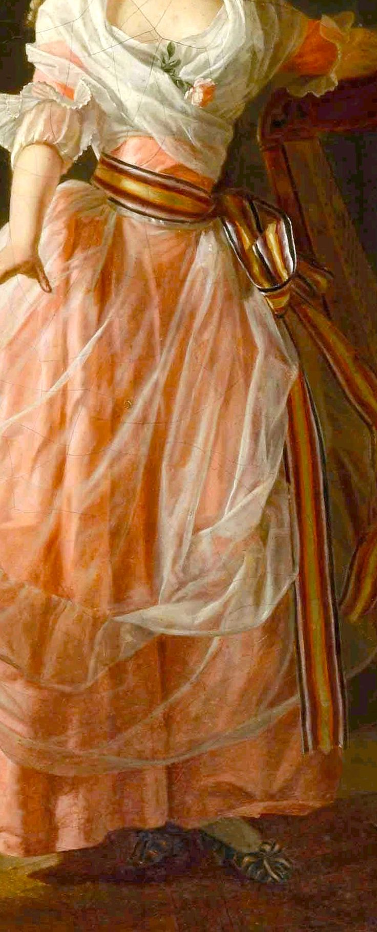 white silk gauze apron with flounce over an pink apricot silk gown with matching white silk gauze ruffle to elbow length tight sleeves, contrasting chocolate brown, gold and red striped length of ribbon tied about tiny waist and extending the length of gown, matching striped shoes, white silk gauze fichu crossed over breasts (and tied in back) Detail from La jeune musicienne, 1788, Michel Garnier