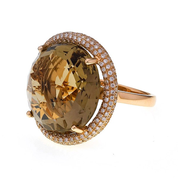 A striking round cut smokey quartz ring, of 20.26cts, with a pavé set round brilliant cut diamond surround, all mounted in a fine and elegant 18ct rose gold setting