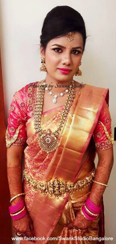 Our bride Aathmiya looks radiant for her reception. Makeup and hairstyle by Swank Studio. Pink lips. Jhumkis. Statement necklace. Bridal jewelry. Bridal hair. Silk sari. Bridal Saree Blouse Design. Indian Bridal Makeup. Indian Bride. Gold Jewellery. Statement Blouse. Tamil bride. Telugu bride. Kannada bride. Hindu bride. Malayalee bride. Find us at https://www.facebook.com/SwankStudioBangalore