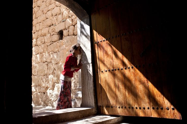 A Yazidi girl enters the temple in Lalish, Iraq, the Yazidi holy sanctuary. Tens of thousands of the Iraqi minority sect have been displaced after being attacked by the Islamic State militant group. They are spilling across northern Iraq - sleeping in fields, cars and abandoned buildings - but at least they are safe. Image by Sebastian Meyer. Iraq, 2014.