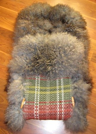 A Norwegian tradition is the use of sheepskin. Some times it is made with a (aakle) Skillbragd coverlet woven in a twill diamond overshot pattern using homespun and dyed wool. This is a bag for babies