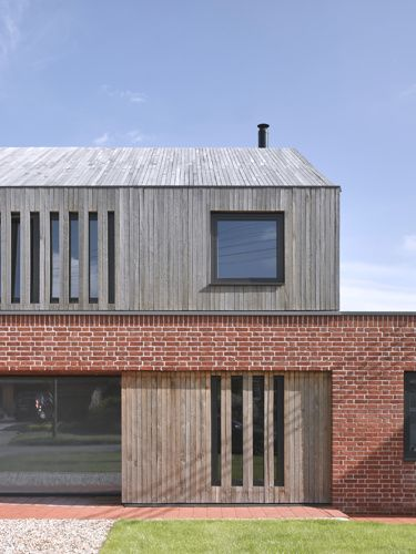 This new build home in Suffolk by Nash Baker Architects is constructed from local red bricks laid in lime mortar, with ribbons of oak clad around the first floor and across the roof.