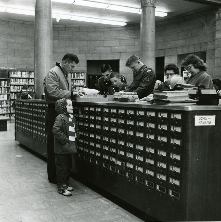 """Using the card catalog - November 20, 1958."" -- In the St. Paul (MN) Public Library. Cute little girl who's amused by something. -- Click through for more historical photos, including one of a wider and higher view of the multiple card catalogs."
