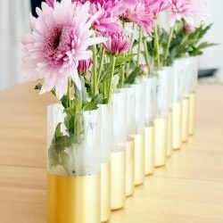 Repetition is key with this upcycled project!  Water bottles make a centerpiece with tons of impact when gilded in gold and grouped together
