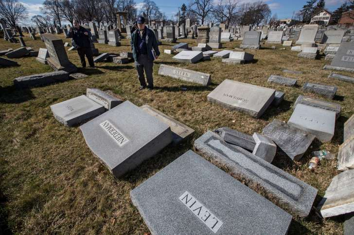 Northeast Philadelphia Police Detectives Nick McReynolds, left, and Thomas Walsh look over headstones that were vandalized at Mount Carmel Cemetery in Philadelphia on Sunday, Feb. 26, 2017. More than 100 headstones have been vandalized at the Jewish cemetery in Philadelphia, damage discovered less than a week after similar vandalism in Missouri, authorities said. (Michael Bryant/The Philadelphia Inquirer via AP)