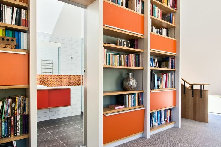 Orange storage and shelving unit in family home by Parsonson Architects