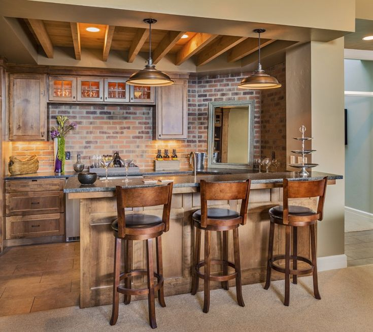This home bar features a dark stained wood on the cabinetry and bar island. Behind the counter is a rustic brick wall, well lit by the warm perimeter lighting around the cabinetry.