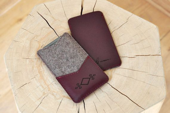 Exclusively looking handmade phone case with cardholder will delight you with sustainability and quality of used materials. The front side of the case is made from 100% natural Lithuanian wool felt, that will perfectly protect the phone, especially it's screen. The front pocket of the case is made from genuine leather (Burgundy colour) and engraved with ethno symbol. This pocket might be used for business or bank cards. The back side of phone case is made from genuine Burgundy leather as…