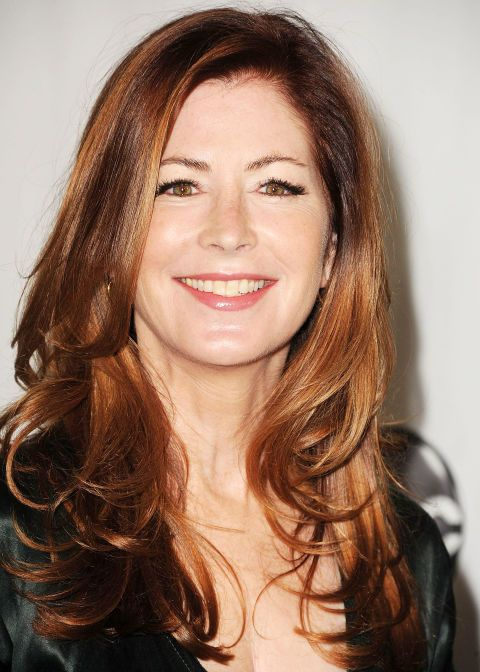 Dana Delany rocks gentle curls with a red glow. Her long, side-swept layers and bounce give her look a youthful feel. Born with straight hair? Take a 2-inch curling iron and curl strands away from the face.