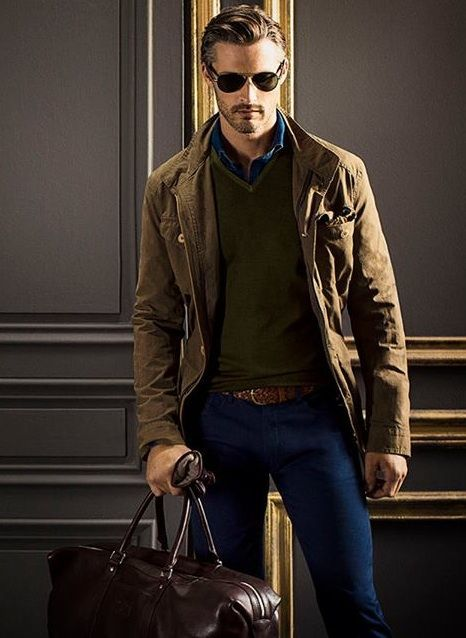 To create an outfit for lunch with friends at the weekend wear a brown military jacket and blue slim jeans. Shop this look for $321: http://lookastic.com/men/looks/sunglasses-longsleeve-shirt-v-neck-sweater-military-jacket-belt-gloves-skinny-jeans-holdall/5140 — Dark Brown Sunglasses — Navy Longsleeve Shirt — Olive V-neck Sweater — Brown Military Jacket — Brown Woven Leather Belt — Dark Brown Leather Gloves — Blue Skinny Jeans — Dark Brown Leather Holdall
