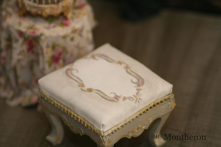 Miniature footstool with hand embroidered upholstery.