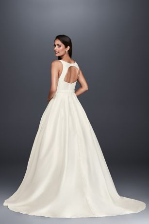 With clean lines and a simple silhouette, this mikado ball gown is for the bride who wants to make an elegant statement. The seamed, high-neck bodice leads to a keyhole back. Covered buttons accent th