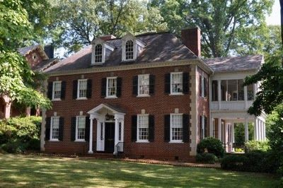 Classic brick house with white columns, trim and shutters