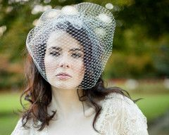 This over-sized wedding birdcage veil is the epitome of vintage elegance. Inspired by 1950's designs, the Amelie is beautifully designed and carefully handmade by the team at Jules.  Featuring a three inch attached comb that has been adorned with a row of luxurious pearls. This French net veil is shown in ivory and also available in white.  We recommend coordinating with Marquis comb, Tamara earrings & Blossom bracelet. €118/$162/£97