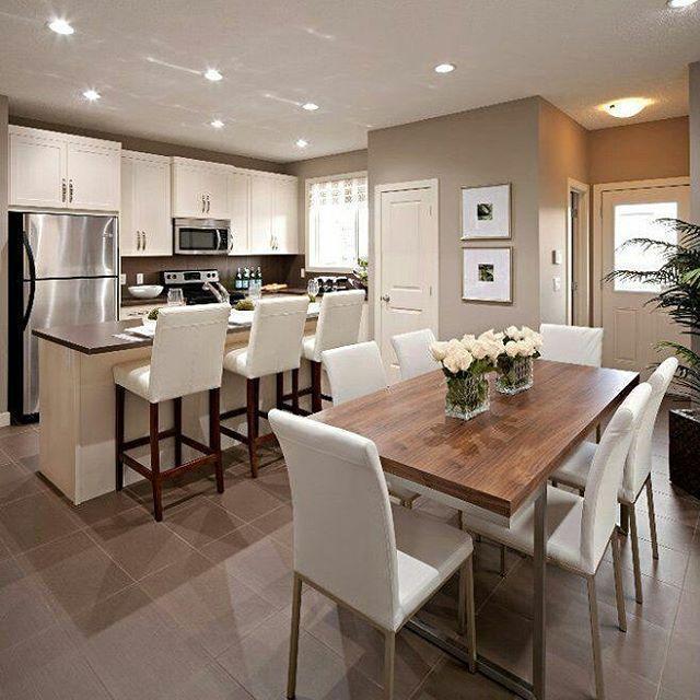 Cozinha integrada com jantar, mesa em madeira com cadeiras e armários brancos, piso creme/bege.