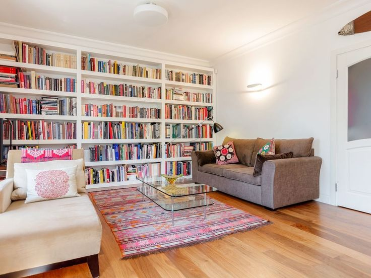 Readers' heaven! Colorful floor to ceiling bookshelves in this London vacation rental looks like heaven!