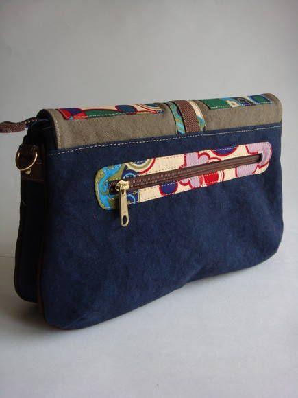 Esta bolsa possui divisória e alça removível. Pode se transformar em carteira, bolsa de ombro ou transversal. Ela é feita de lona estonada e detalhe da tampa em tecido de algodão.