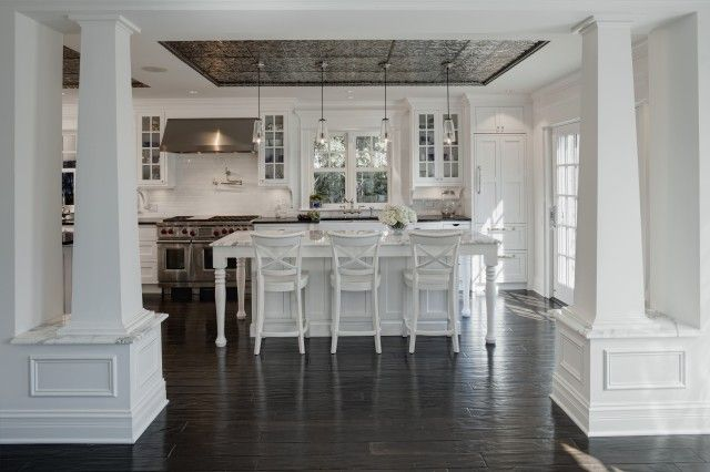 Beautiful kitchen with tin ceiling from American Tin Ceiling, creamy white glass-front kitchen cabinets with Marron Cohiba (Antique Brown Suede) Granite countertops, white kitchen island with turned legs & marble countertop, white counter stools and hand scraped wood floors.