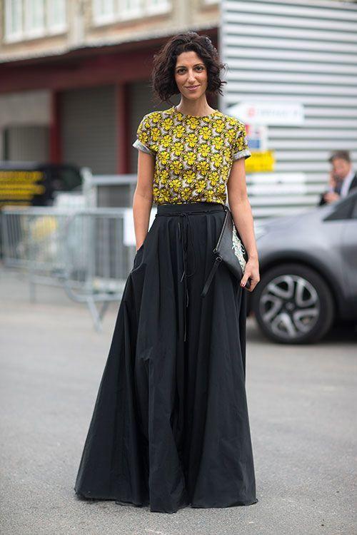 Den Look kaufen:  https://lookastic.de/damenmode/wie-kombinieren/gelbes-t-shirt-mit-rundhalsausschnitt-mit-blumenmuster-schwarzer-falten-maxirock-schwarze-und-weisse-leder-clutch/1408  — Gelbes T-Shirt mit Rundhalsausschnitt mit Blumenmuster  — Schwarzer Falten Maxirock  — Schwarze und weiße bedruckte Leder Clutch