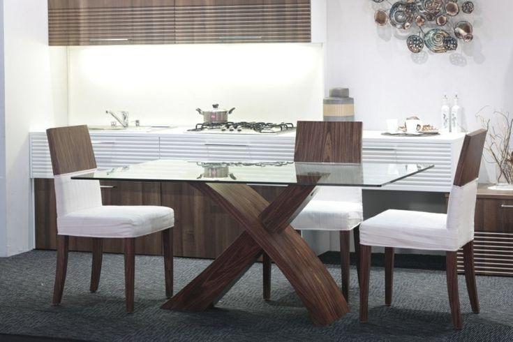 table à manger en bois avec plateau en verre et chaises en bois avec housses blanches dans la salle à manger