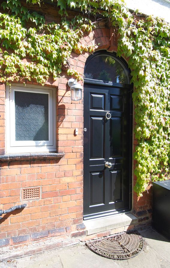 The Awesome Web Traditional panel front door in a black finish equipped with Samuel Heath ironmongery